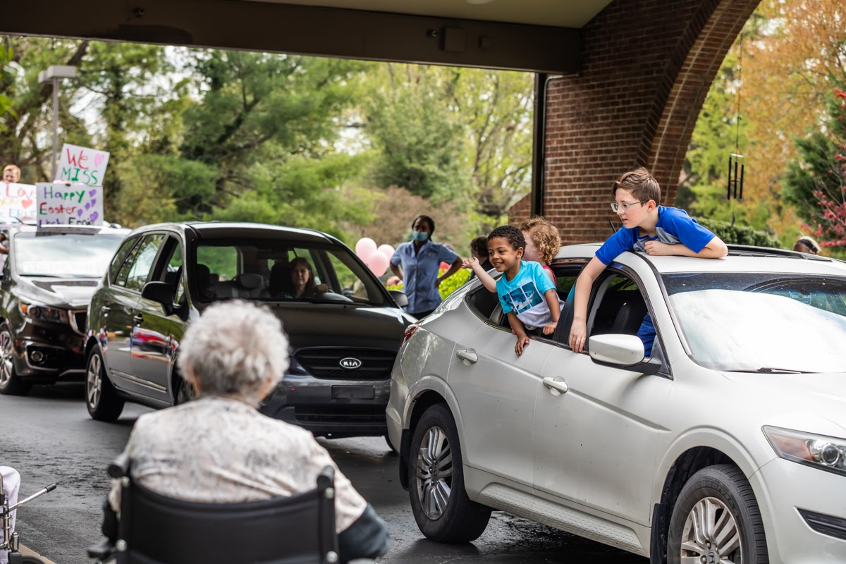 a stream of cars parade by a nursing home, greeting their loved ones through the windows.