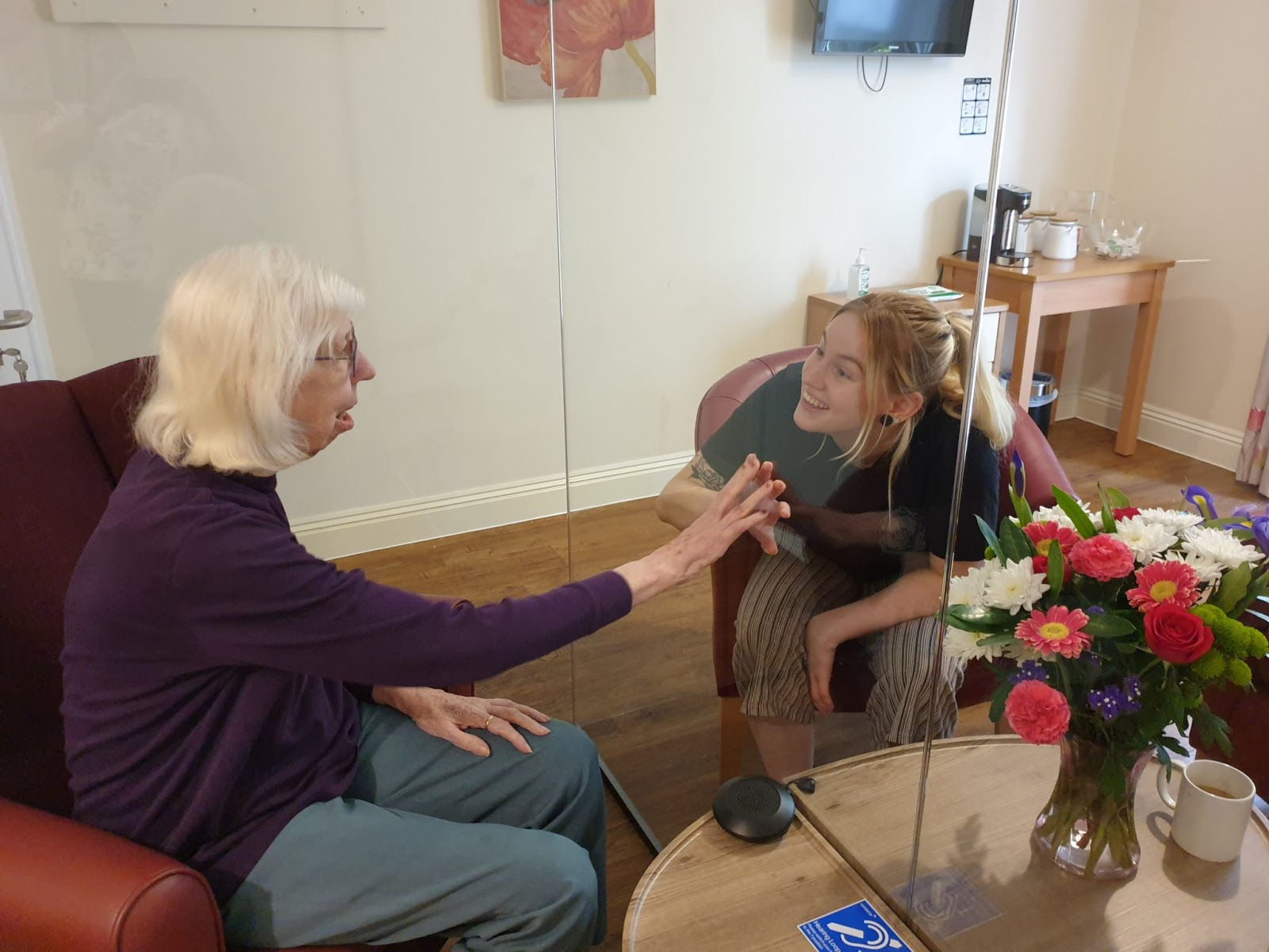 a care home resident greets her visitor through a glass partition