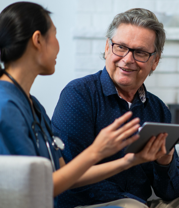 A nurse holds a tablet and is speaking with an older man who is smiling