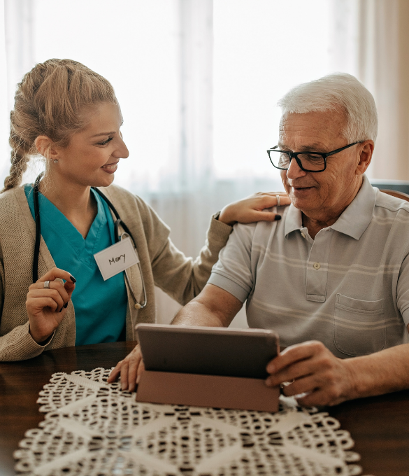A home health nurse shows an older man something on a tablet. She has her hand on his shoulder.