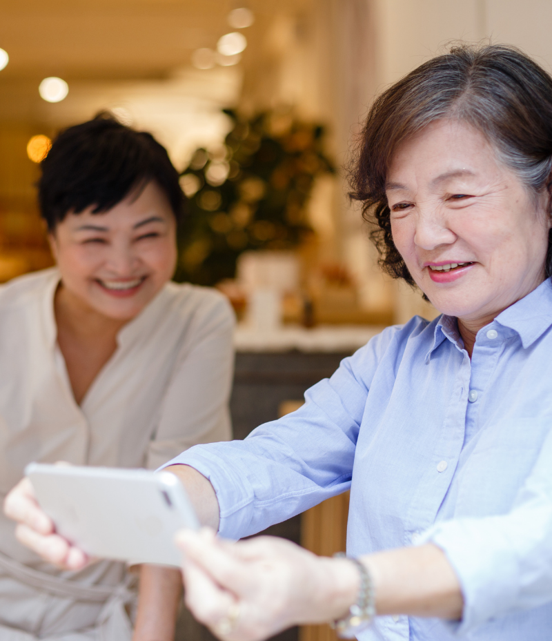 Two Asian women smile and look at a smartphone