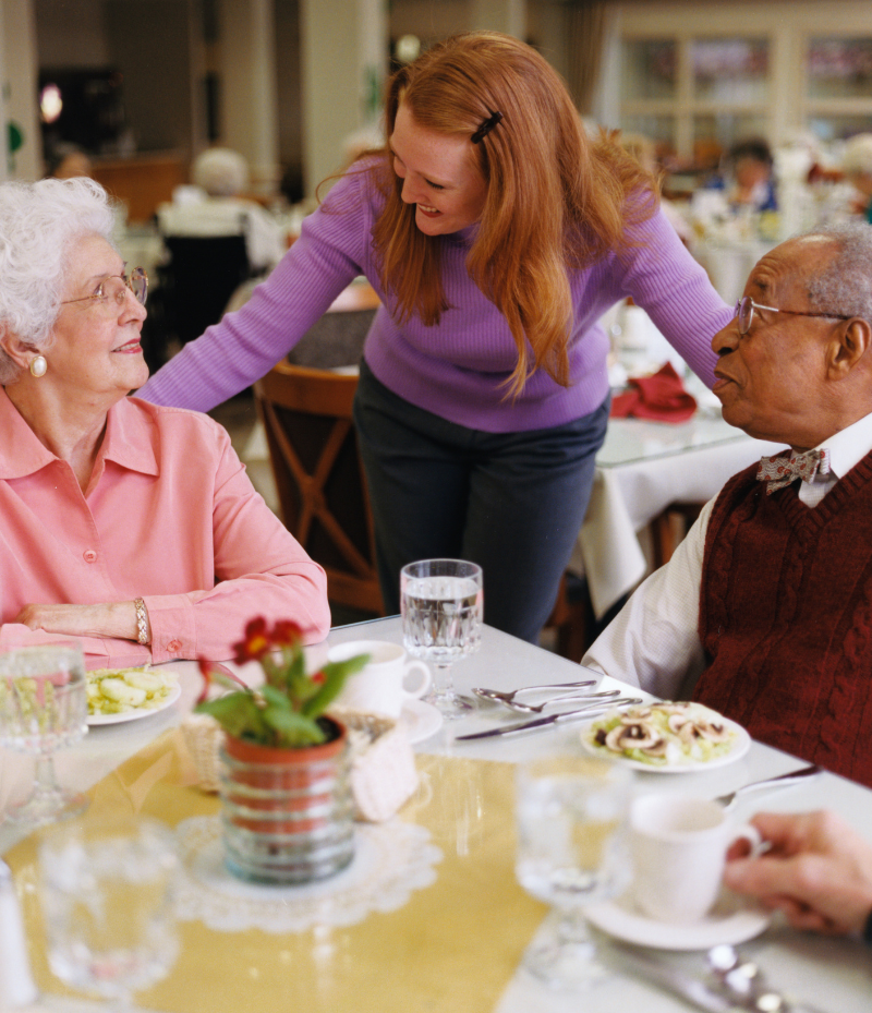 A woman smiles and chats with two elderly people at a dinner table