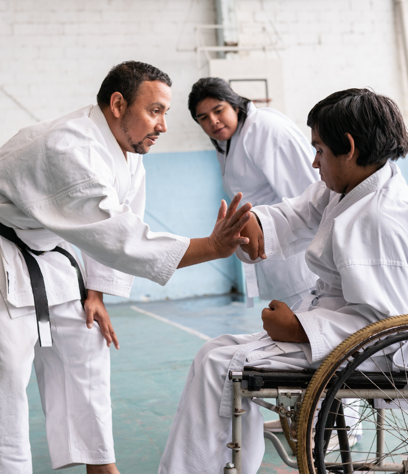 A Tae Kwon Do instructor is helping a participant who is in a wheelchair