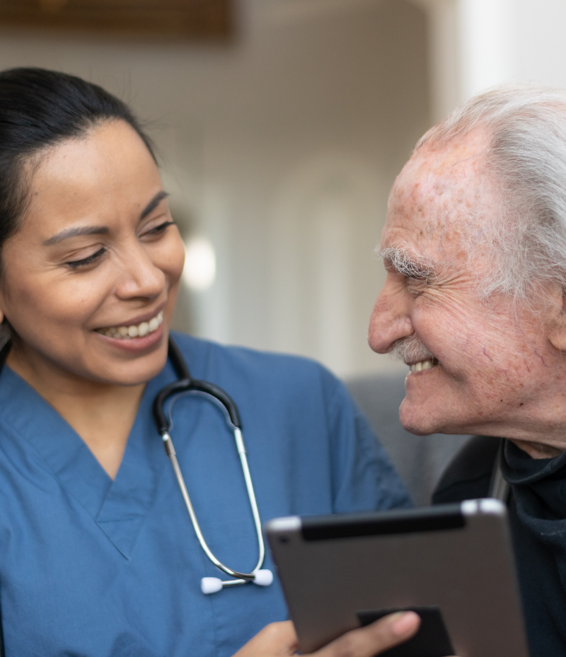 A nurse and her patient are laughing at something funny on the tablet the nurse is holding
