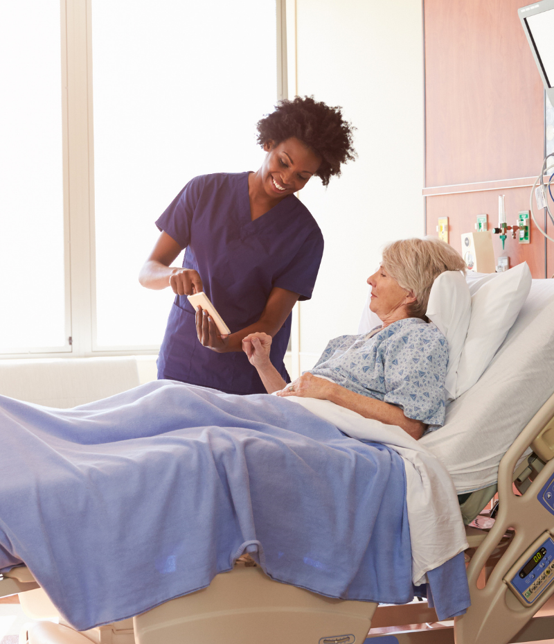 A nurse shows a patient something on her tablet. The patient is in a hospital bed.