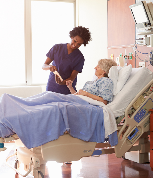 A female nurse is standing beside a patient's hospital bed, showing the woman something on the tablet