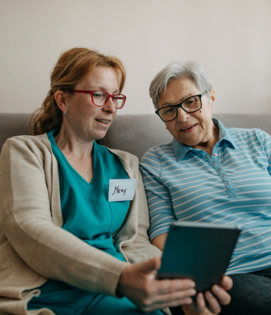 A home health worker shares a tablet with an elderly woman