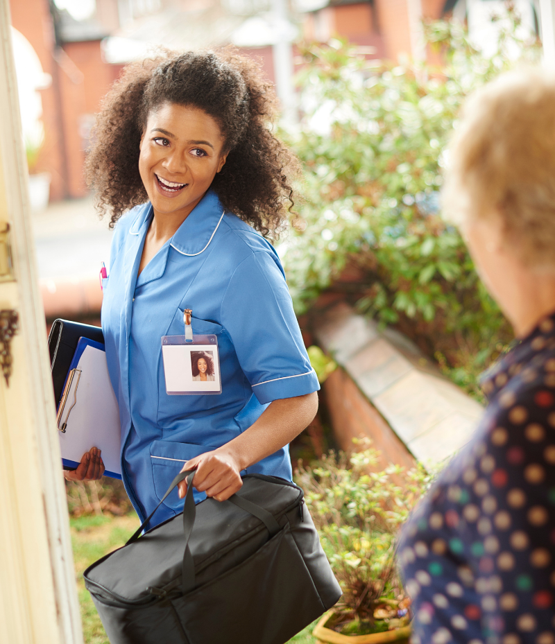 A black woman dressed as a home care aid standing outside someone's door.