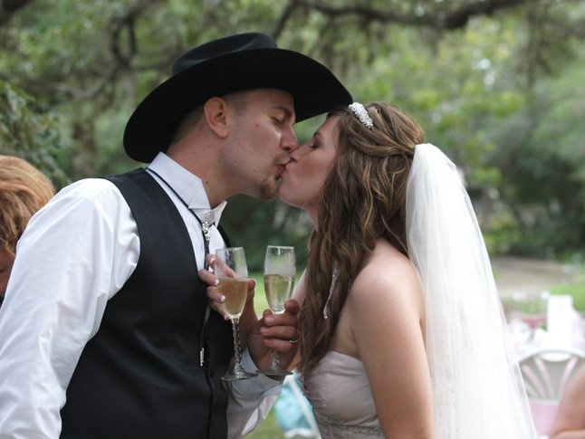 Bride and groom kissing with champagne