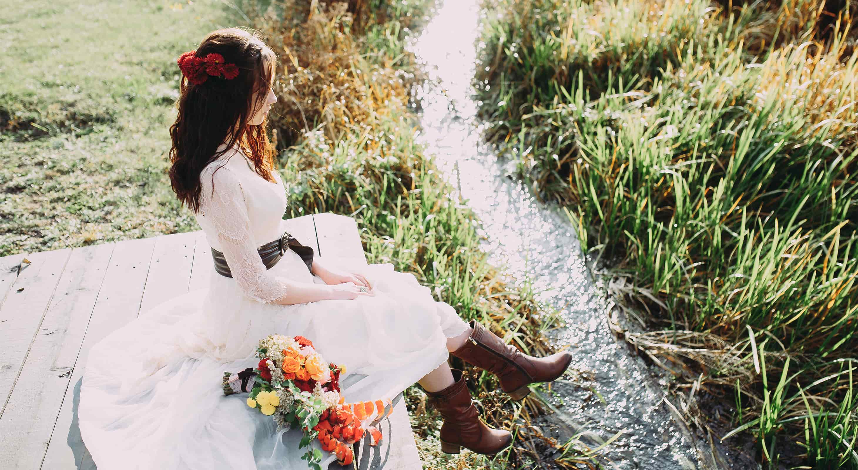 Bride with cowboy boots dangling her feet near a brook