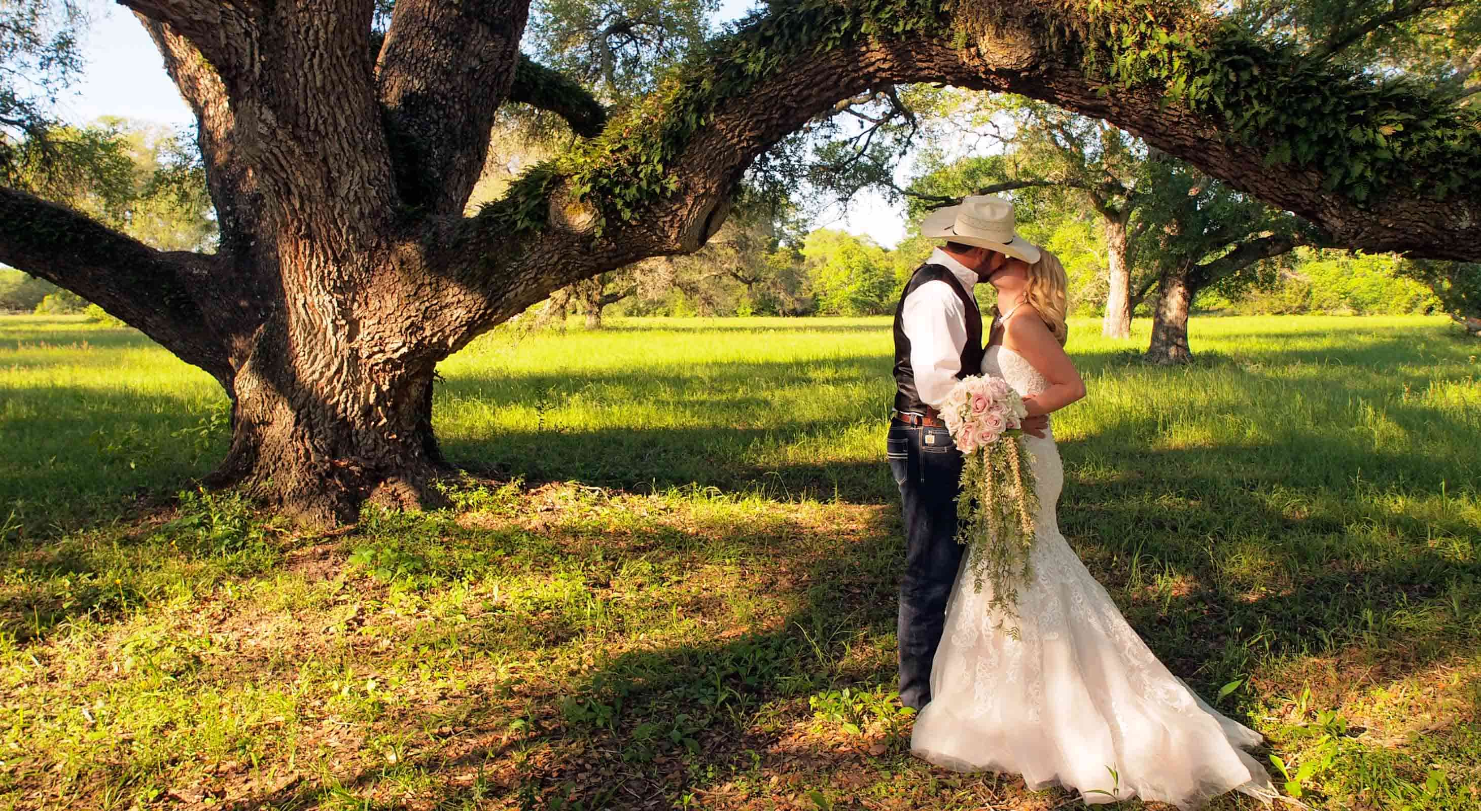 Bride and groom under large oaks at our Texas wedding venue