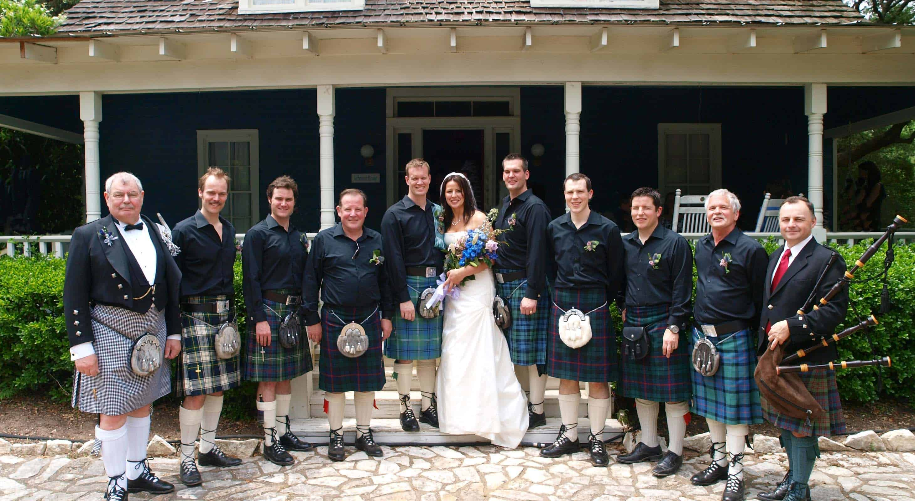 Wedding party in traditional Scottish attire standing in front of BlissWood Ranch