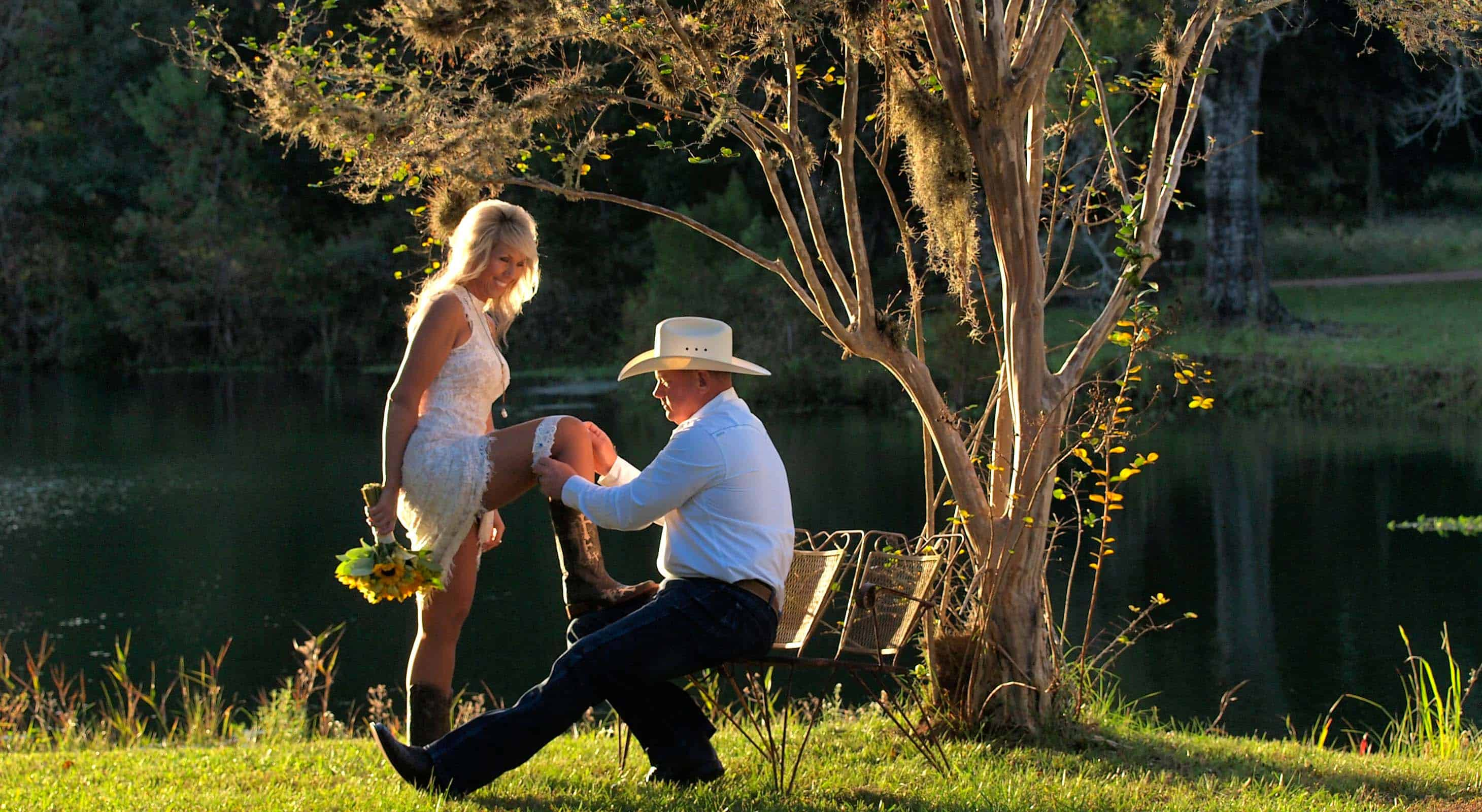 Groom wearing a cowboy hat takes off garter from wife in front of a lake