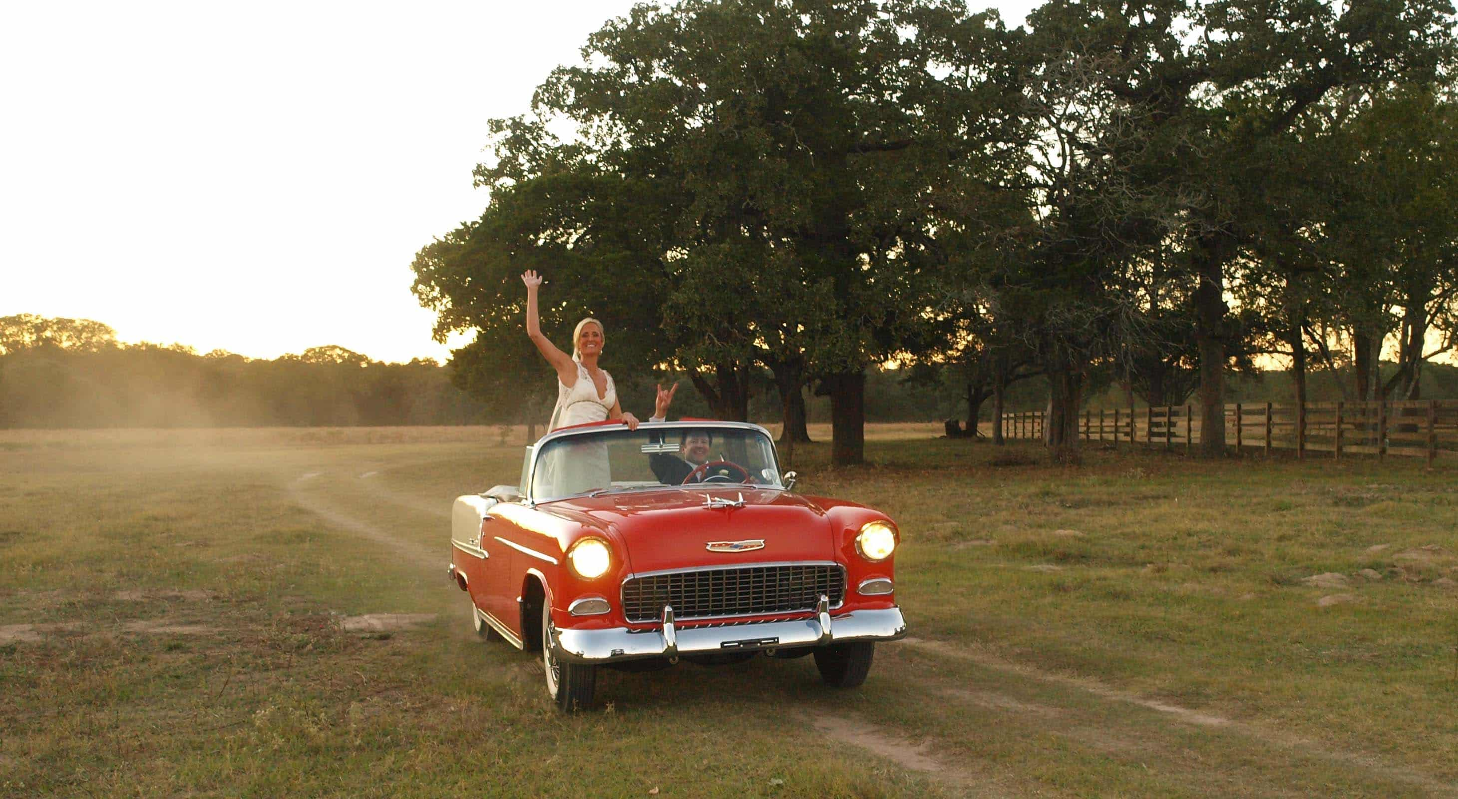 Bride and groom driving in a Red and white classic car on a BlissWood Ranch road