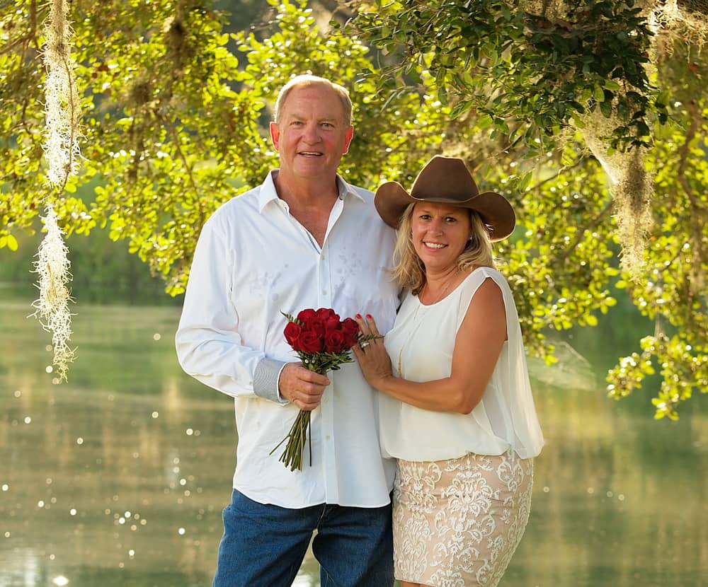 Couple in casual attire standing in front of a lake at Texas wedding venue