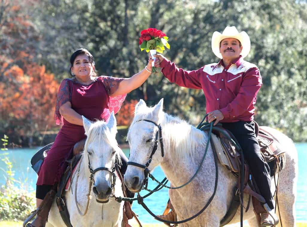 Bride and groom on horseback holding a bouquet of roses at their romantic Texas wedding