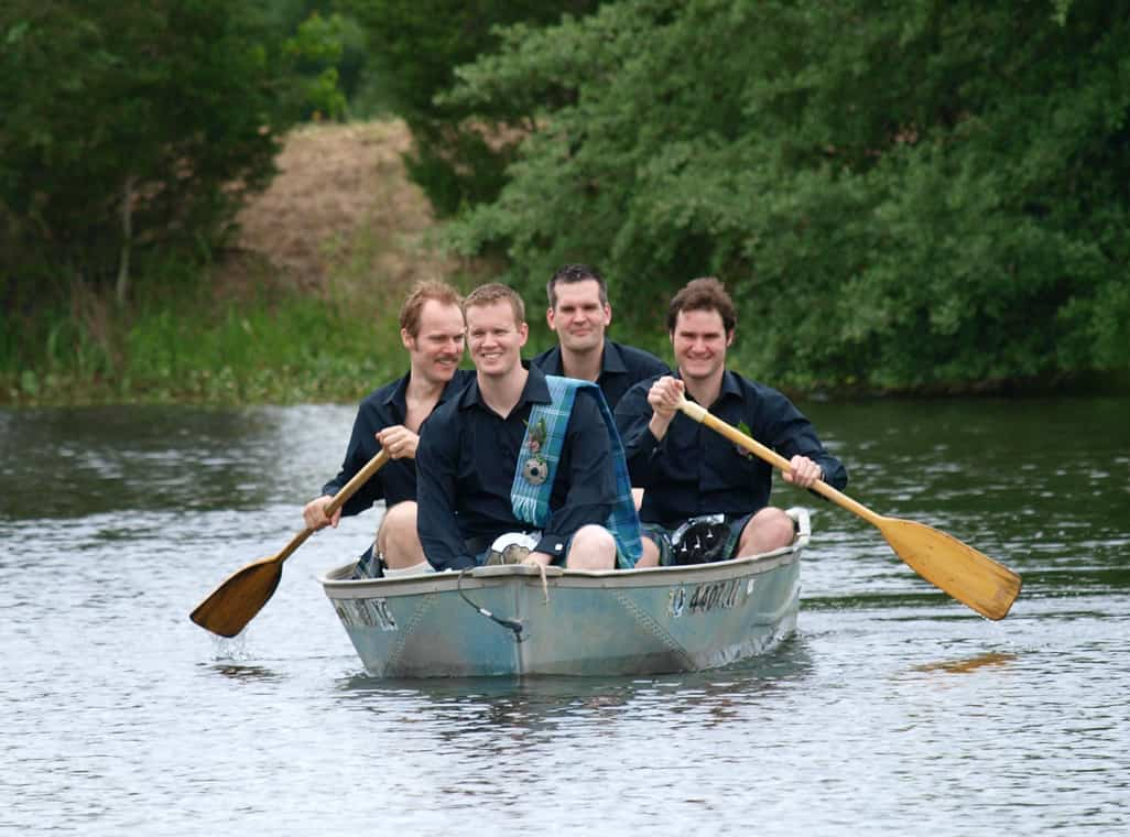 Groomsmen rowing a boat on the lake to deliver the groom