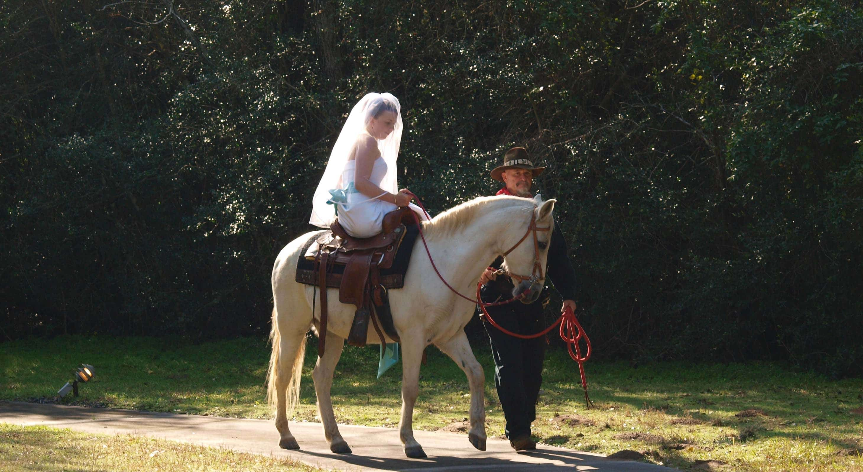 A bride riding a horse side saddle