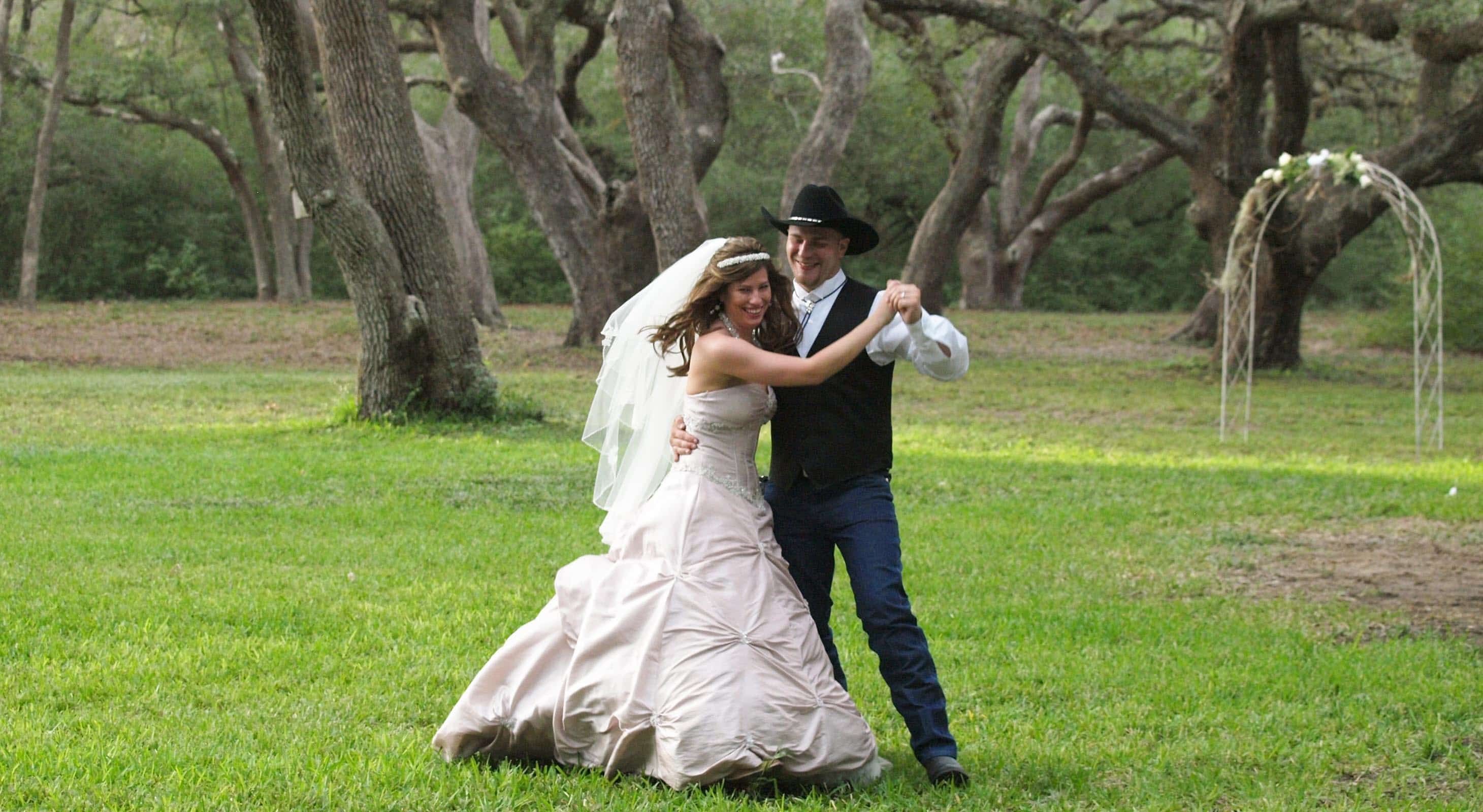 A bride and groom dancing under oaks at a Texas ranch wedding