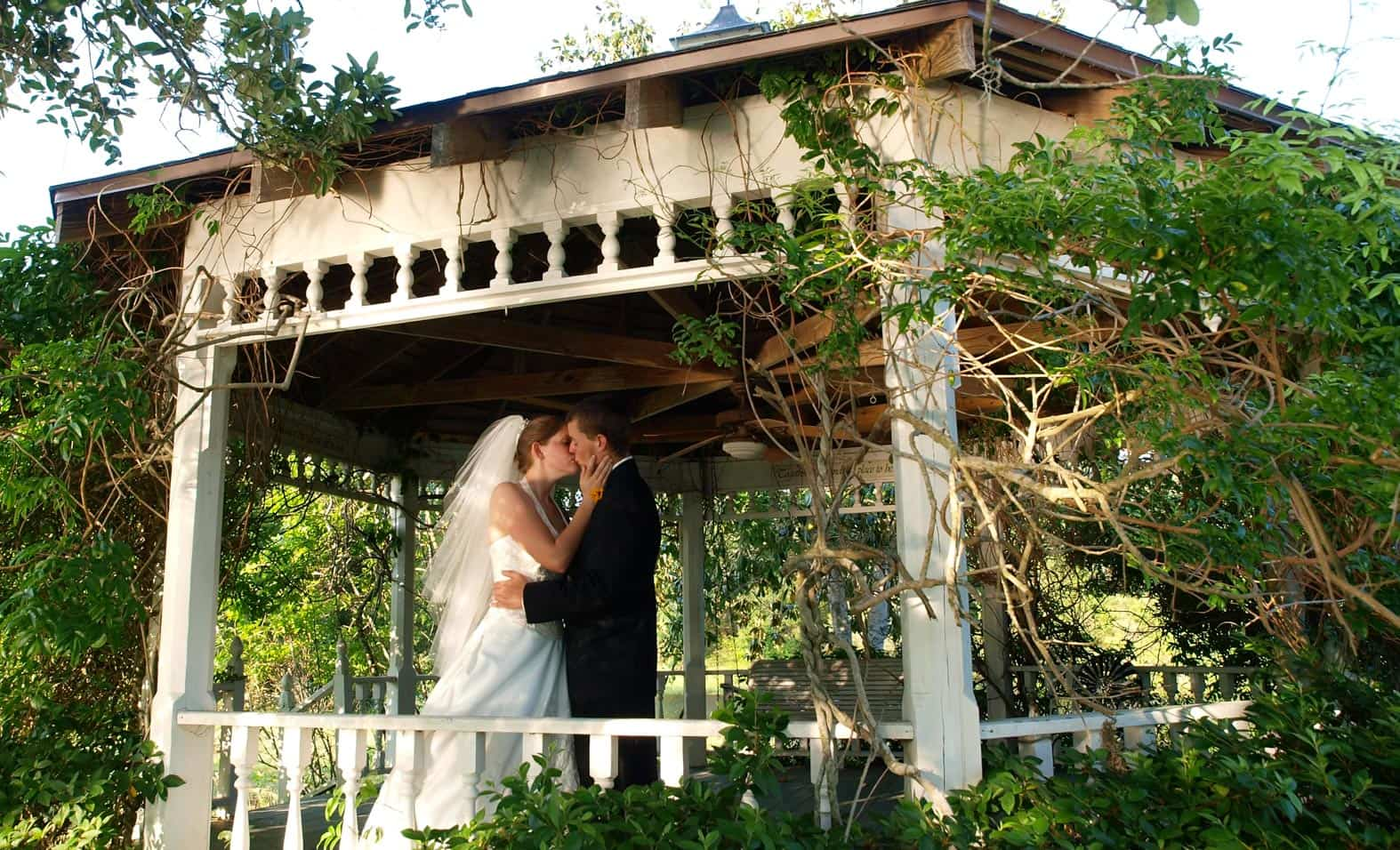 A couple kissing in a white gazebo at our Texas wedding venue