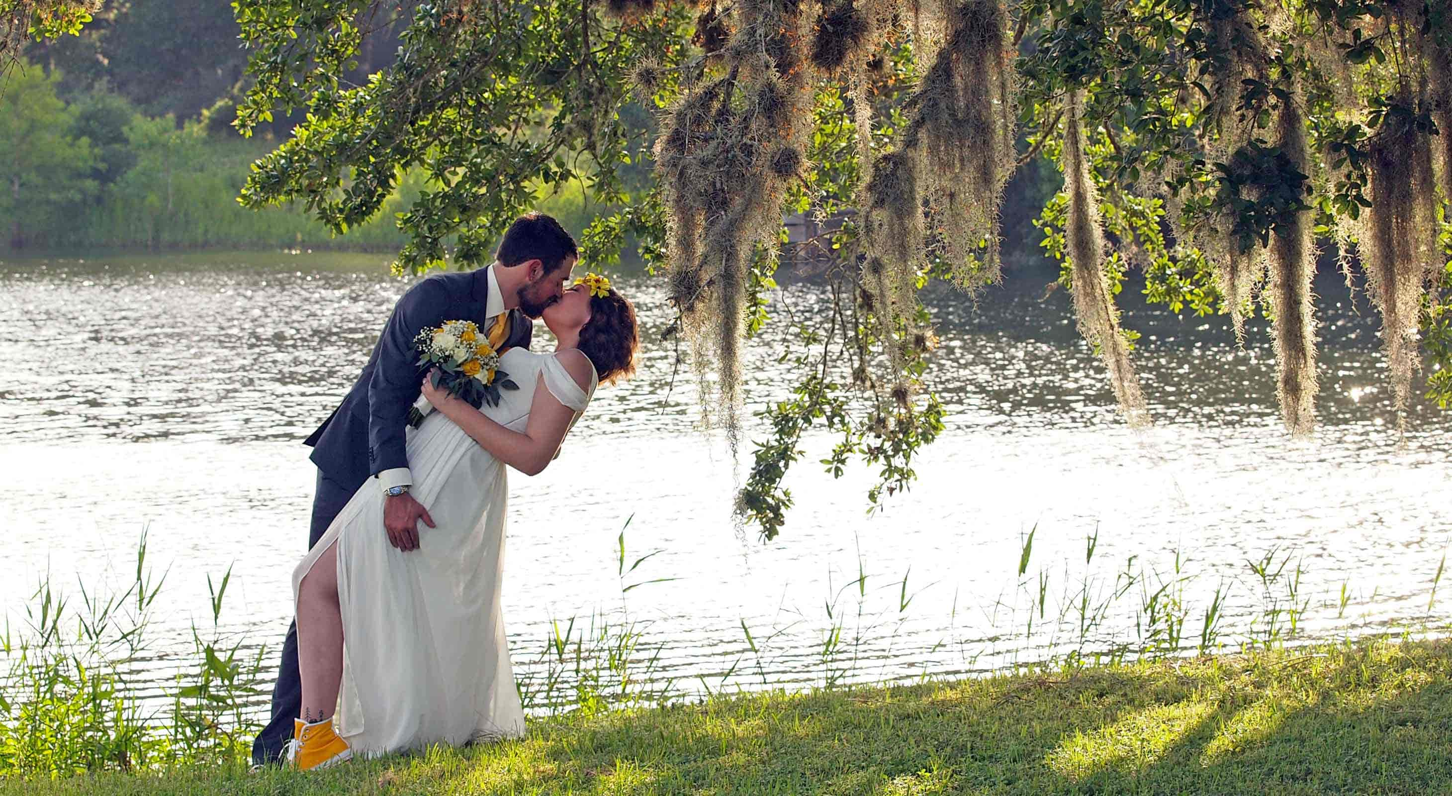 A couple kissing near the shore of a lake at BlissWood Ranch
