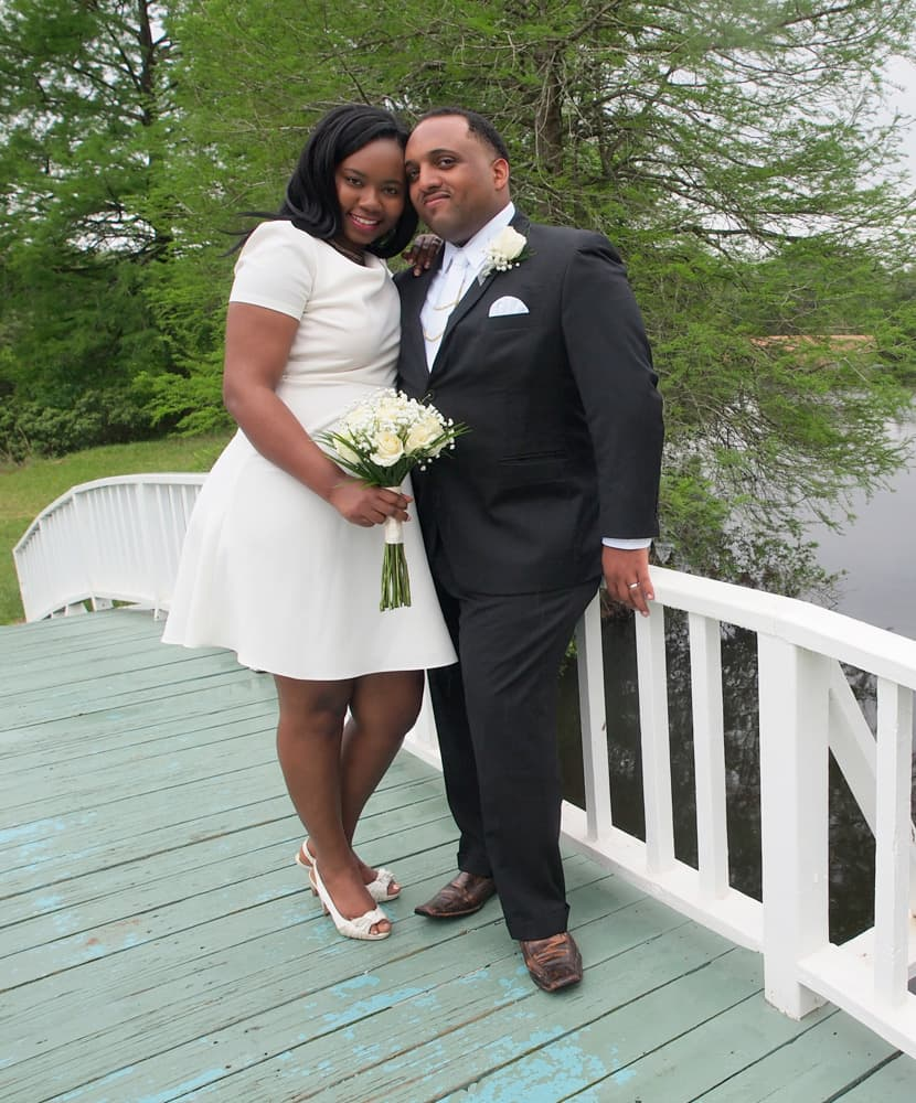 Bride and groom standing on a white curved bridge near a lake