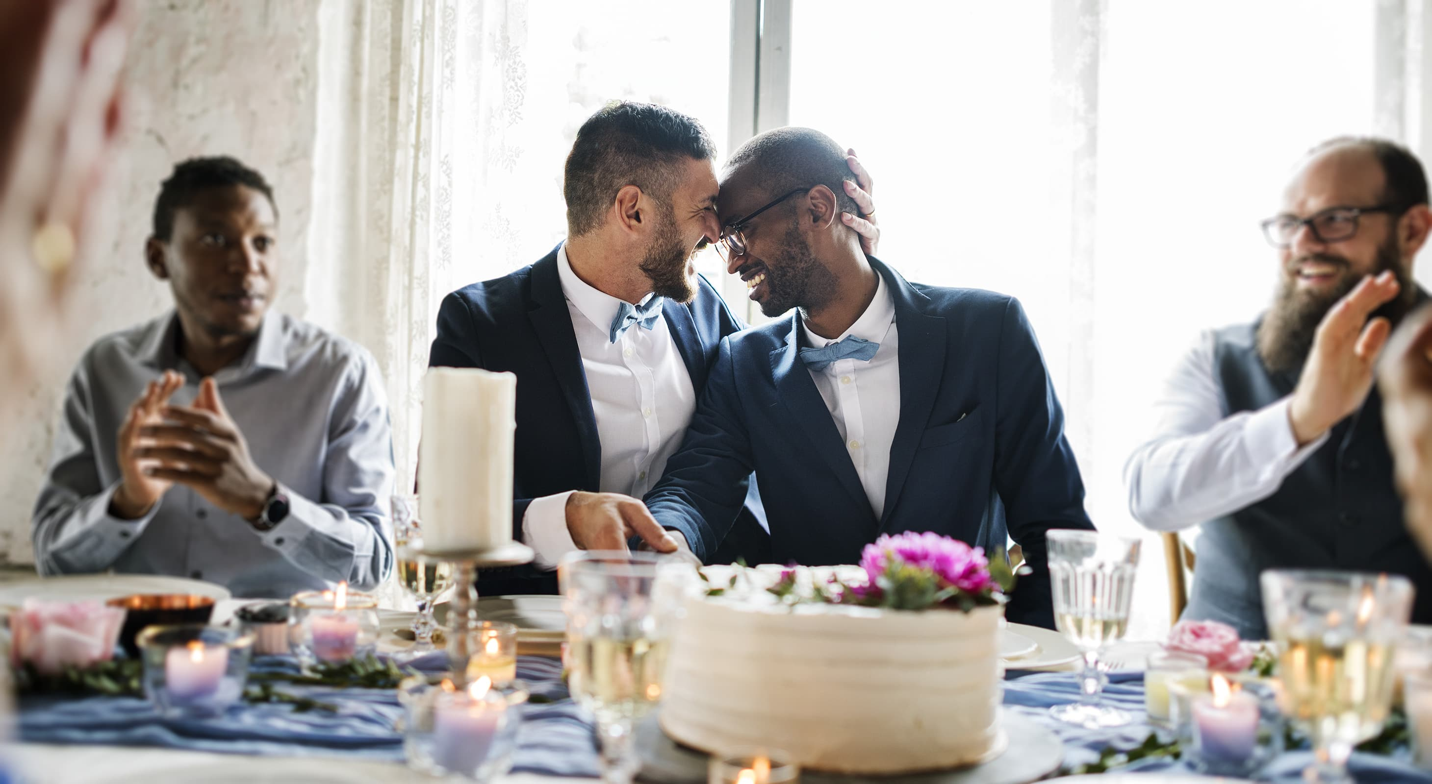 A gay couple embracing and laughing at a dinner reception