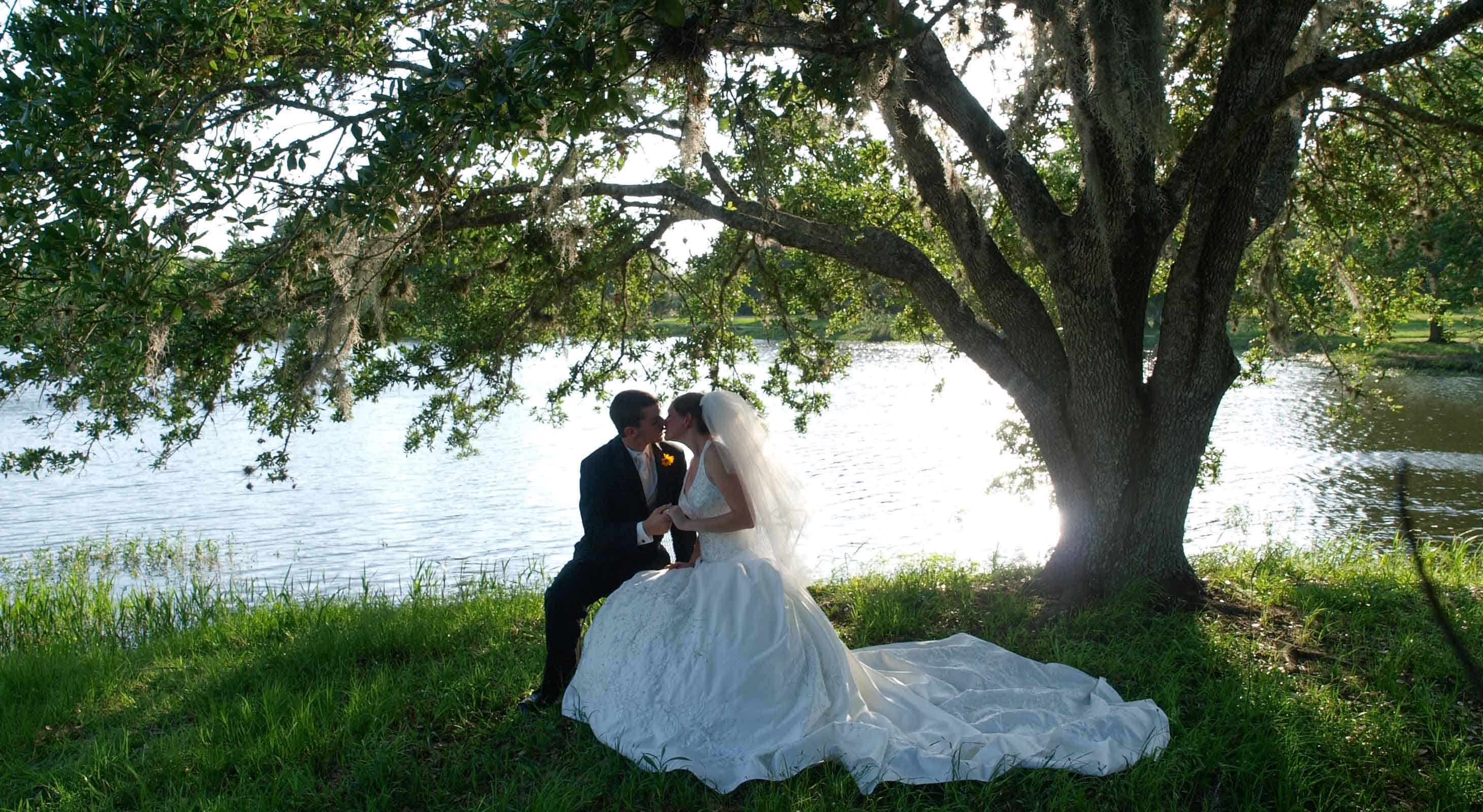 Couple seated under arch of a large oak branch in front of the lake at BlissWood Ranch