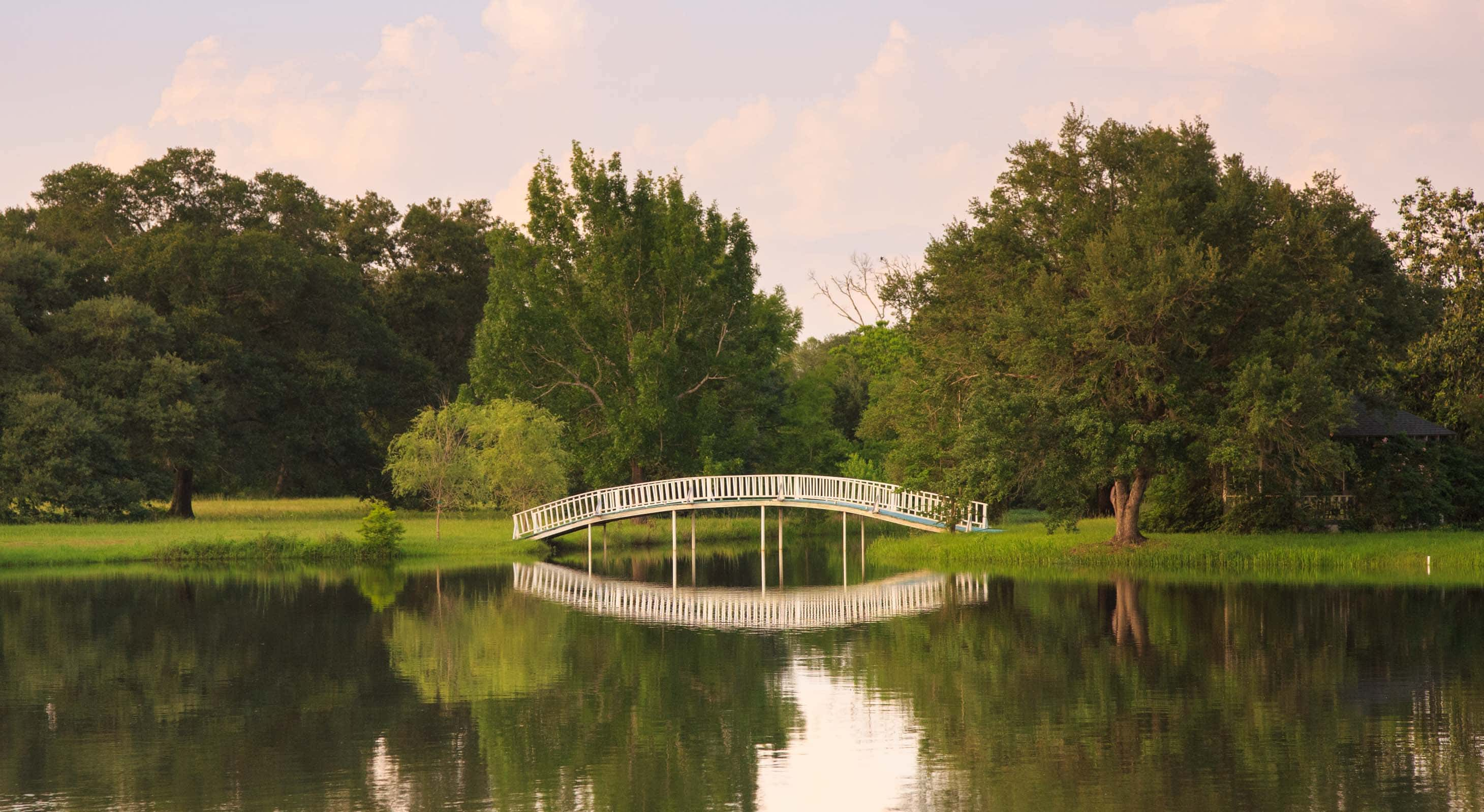 A white arched bride to a small island with a gazebo on it at a Texas wedding venue