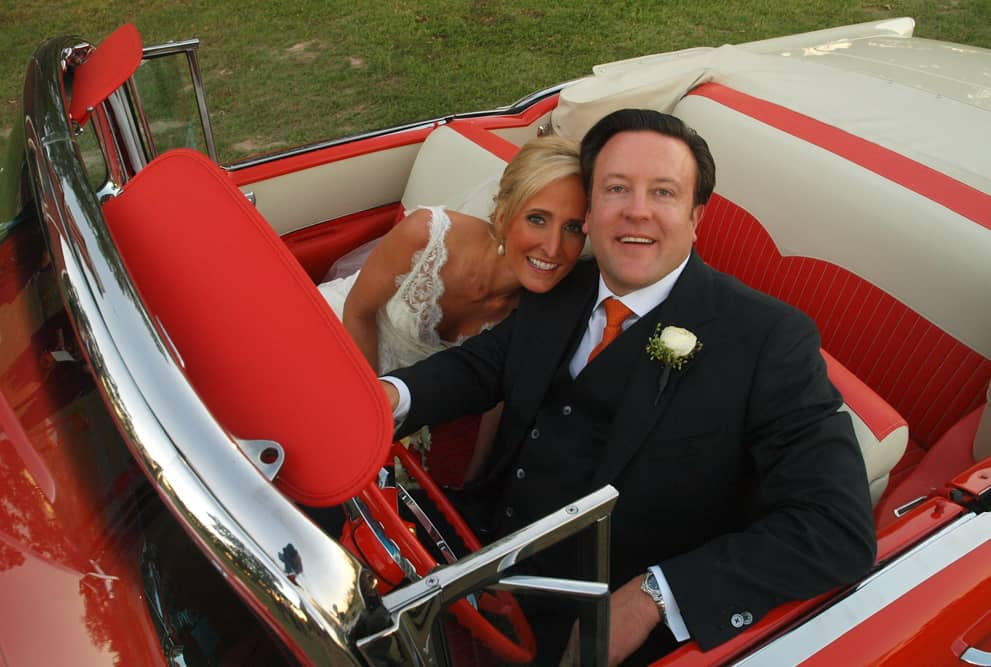 Bride and groom in a classic convertible car