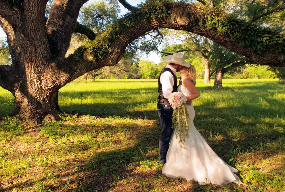 Bride and groom kissing under old oaks
