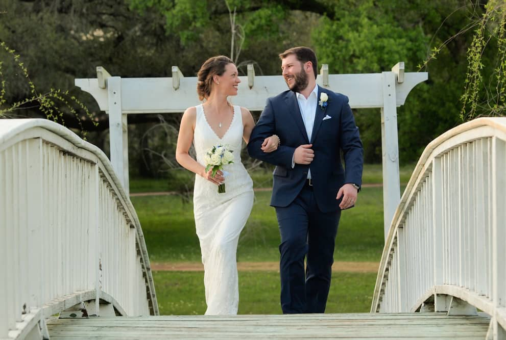 Bride and groom walk over a bridge at BlissWood Ranch wedding venue