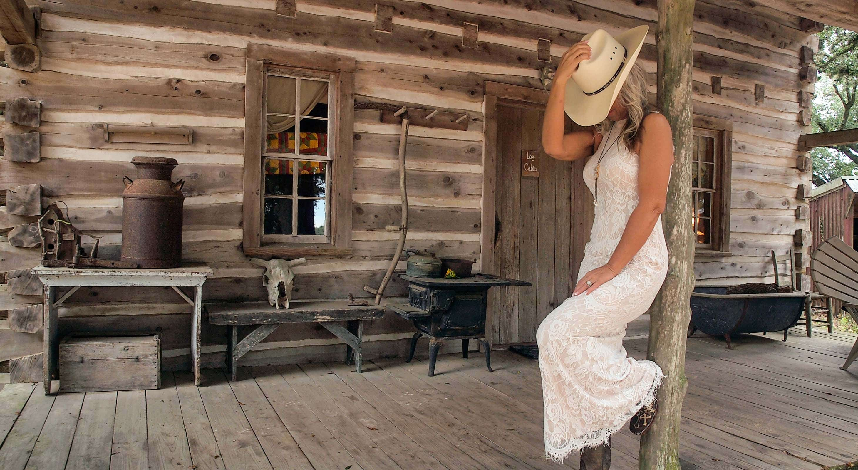 Bride wearing a cowboy hat in front of a rustic log cabin