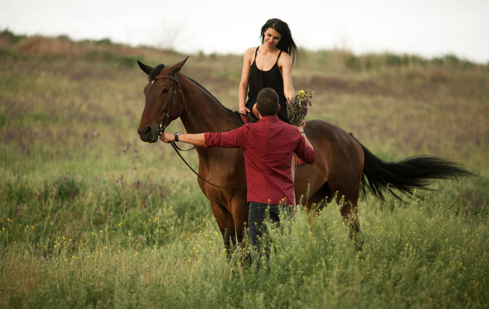 A man gives a bouquet of wildflowers to his partner on a horse