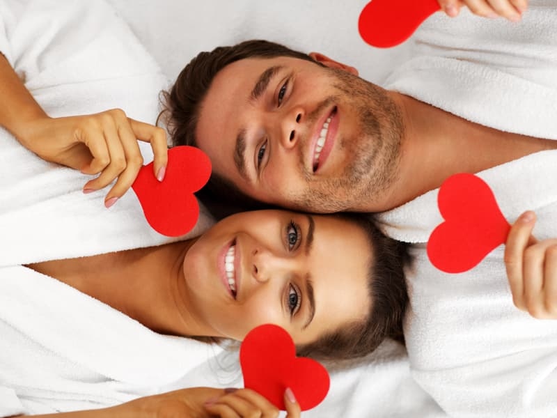 A couple laying down in white bathrobes holding small paper hearts