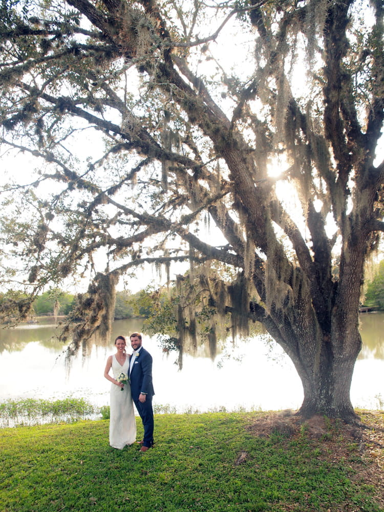 Bride and groom standing under a large oak tree near a lake