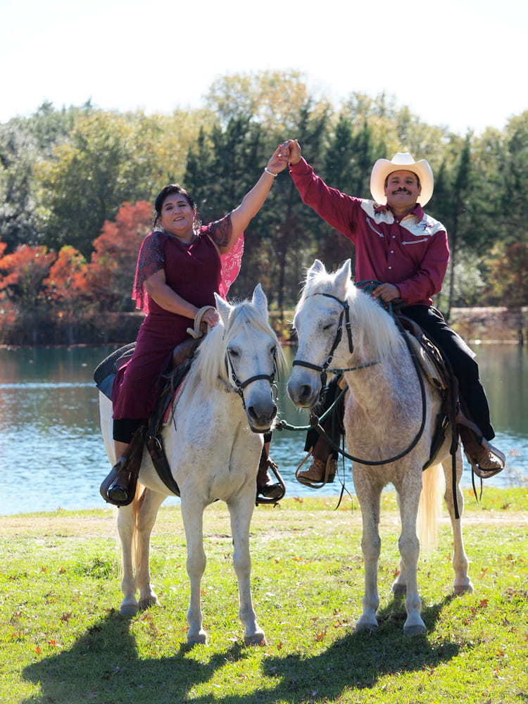Hispanic Couple on horseback holding hands