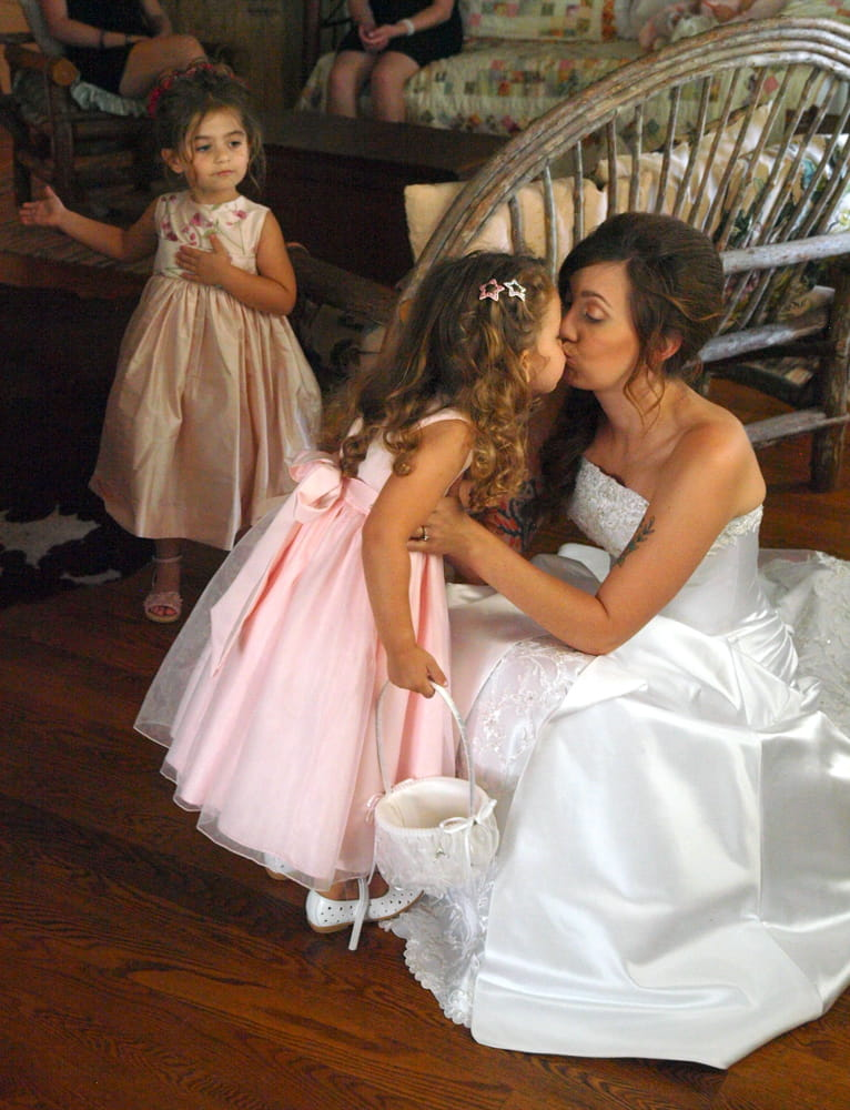 Bride kissing her flower girl daughter