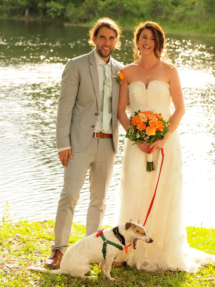 A groom standing next to his bride and their dog