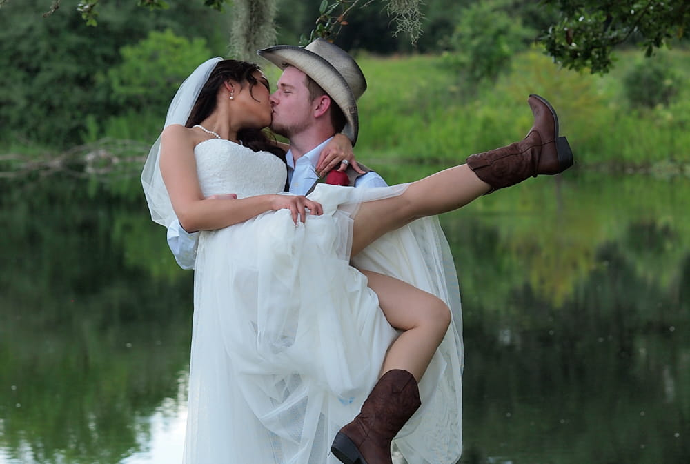 A man in a cowboy hat holding his asian bride