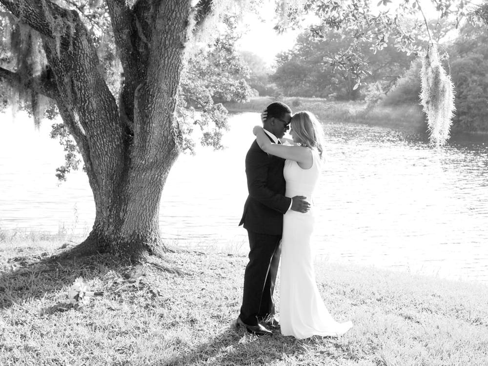 A bride and groom standing on the bank of a lake, a black and white photograph