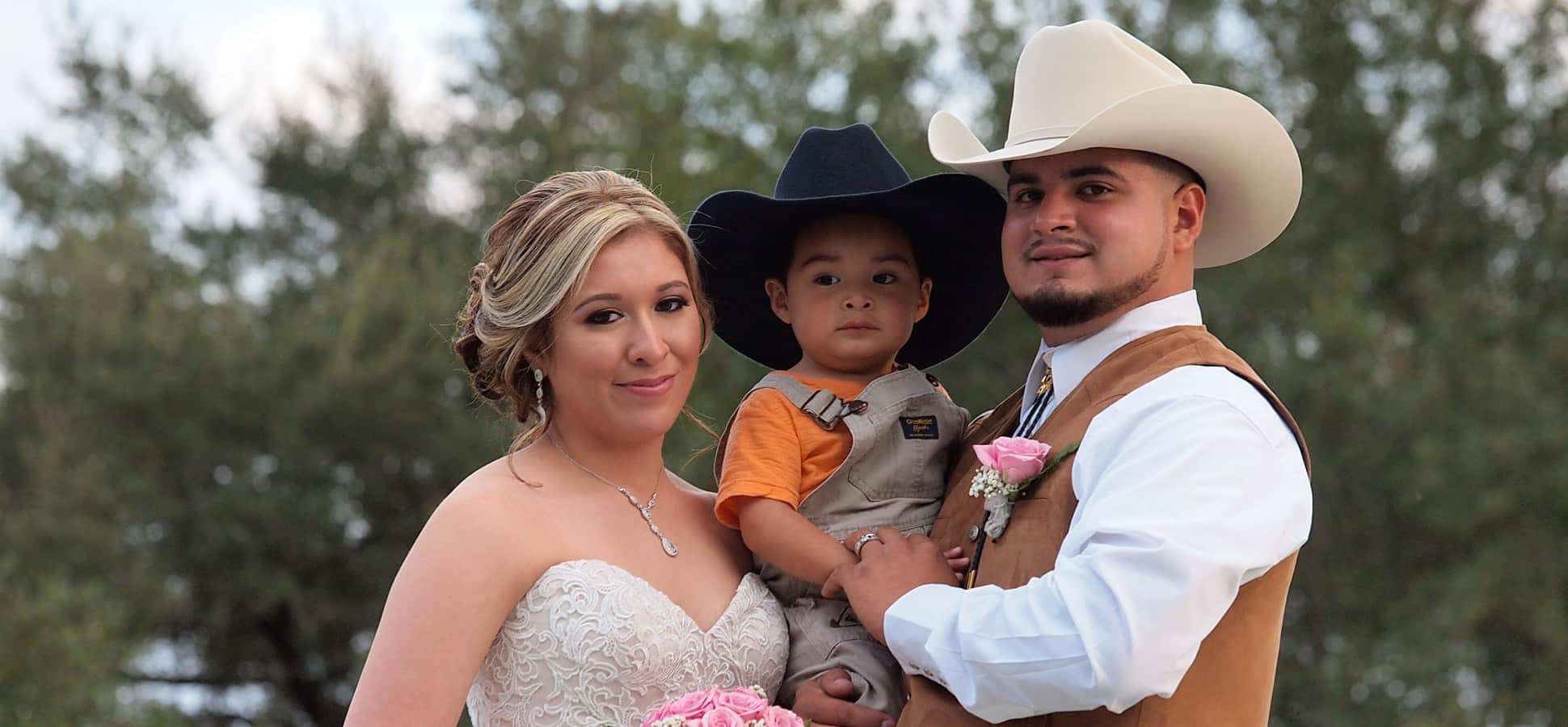 A couple holding a small child on the bride at BlissWood Ranch wedding venue