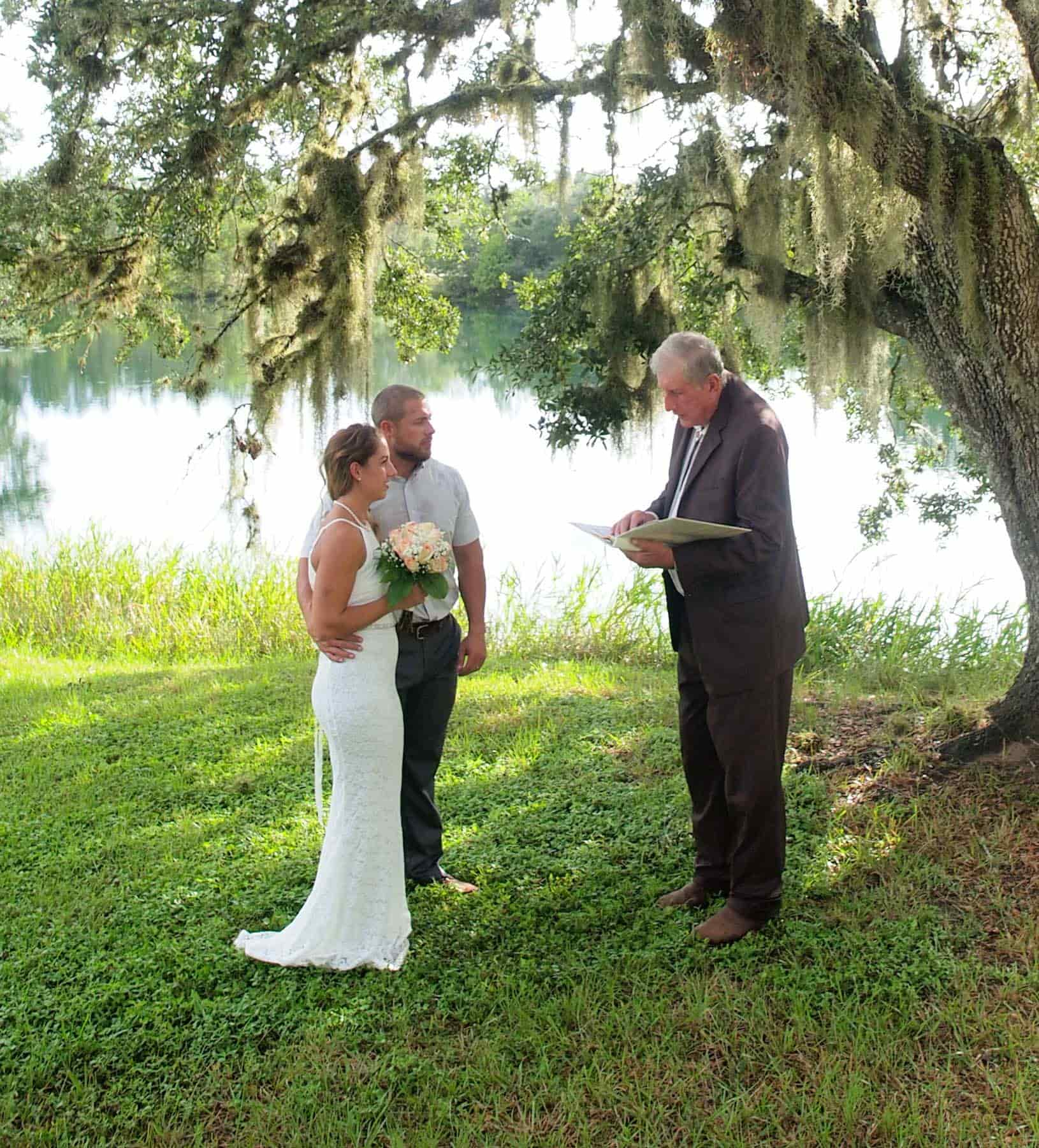 Couple eloping under a tree in front of a lake
