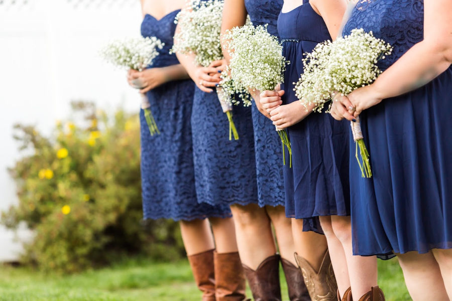 Bridesmaids in blue dresses holding flowers