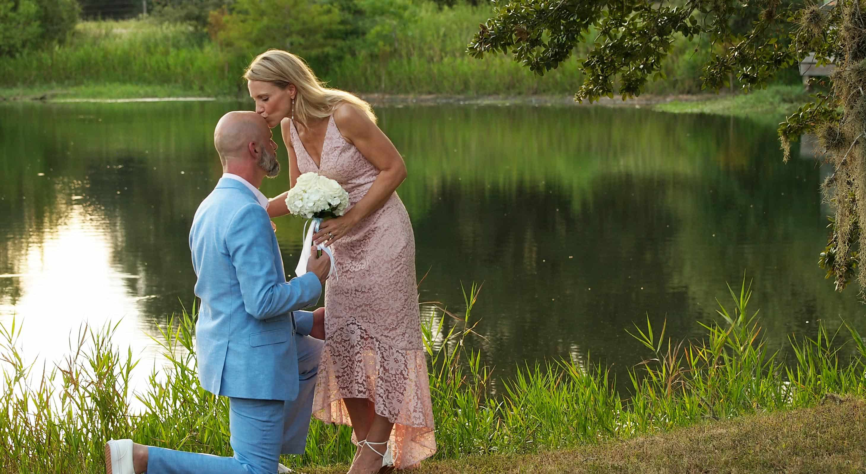 Man on one knee in front of his wife in front of a lake