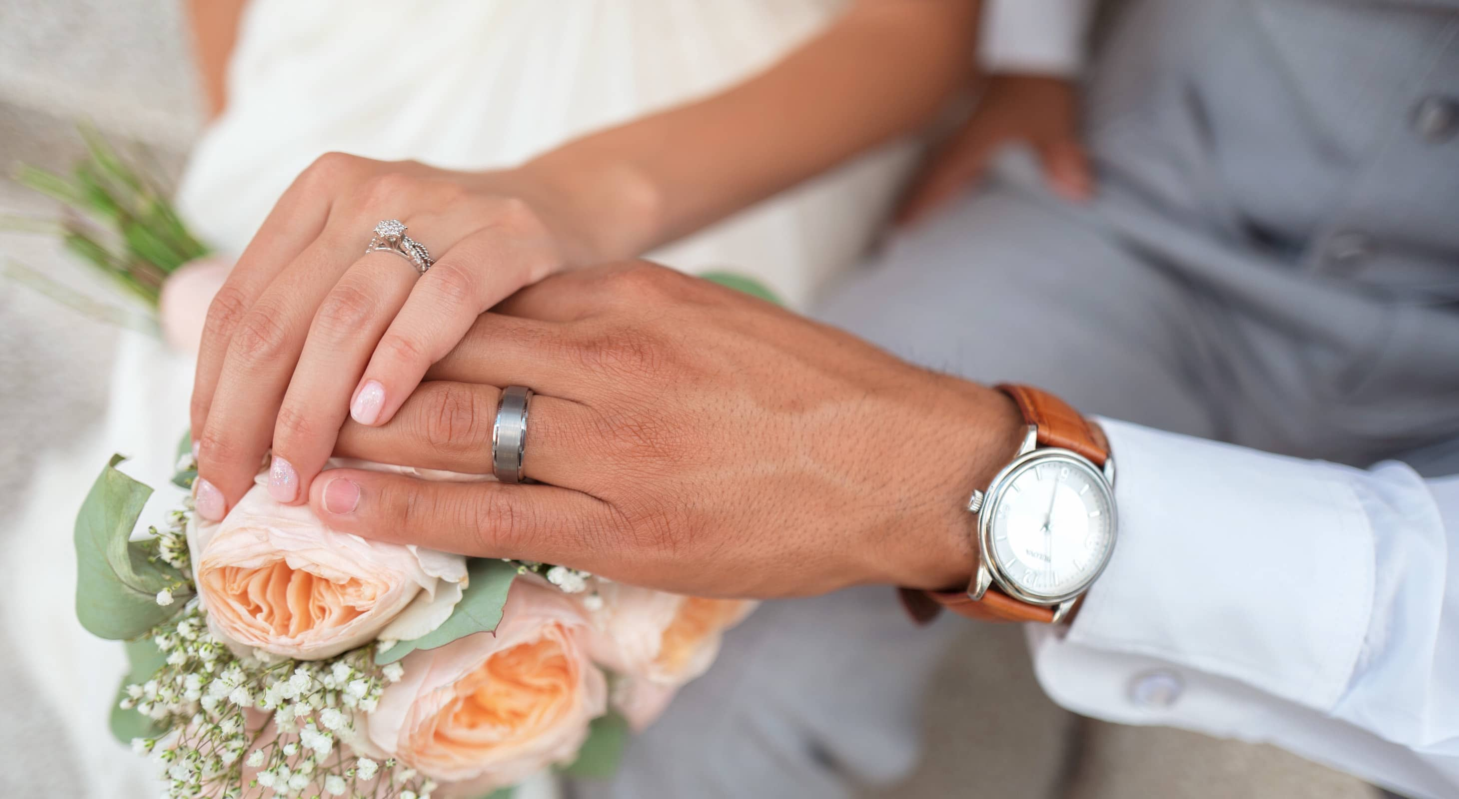 Close up on two hands holding a bouquet