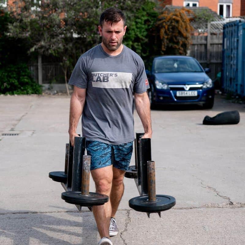 man carrying strongman equipment