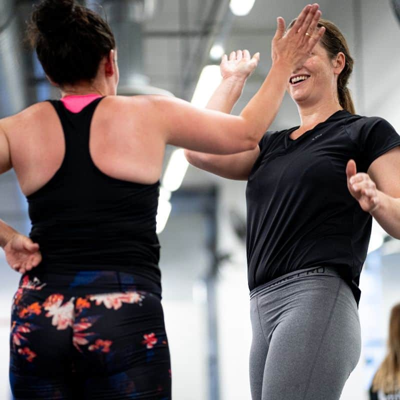 Corporate clients high five after gym workout