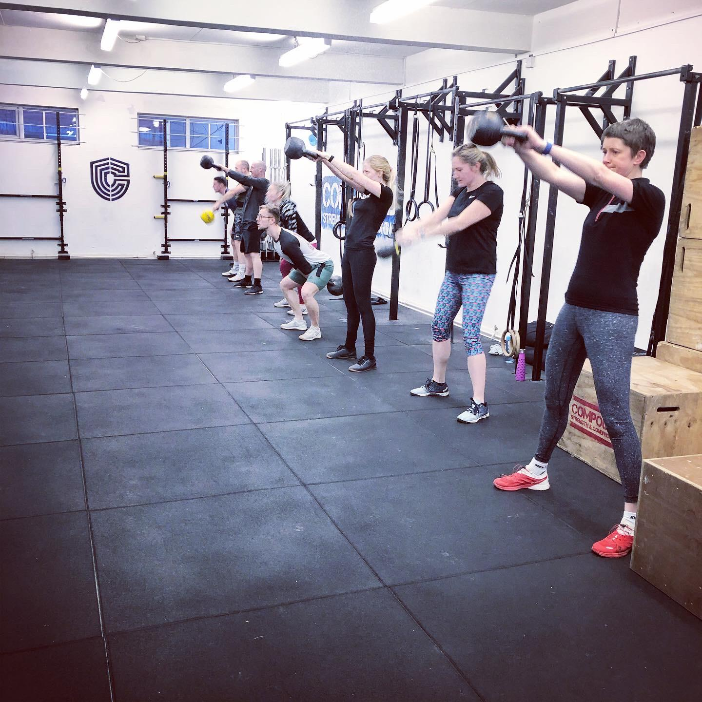 People training with kettlebells in gym