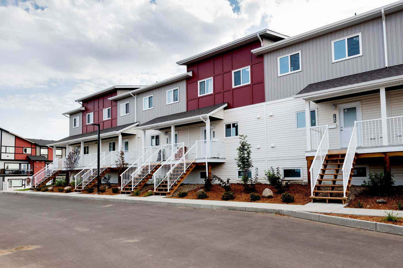A view of the Cory Villas townhouses that shows the three-bedroom raised suites with a porch.